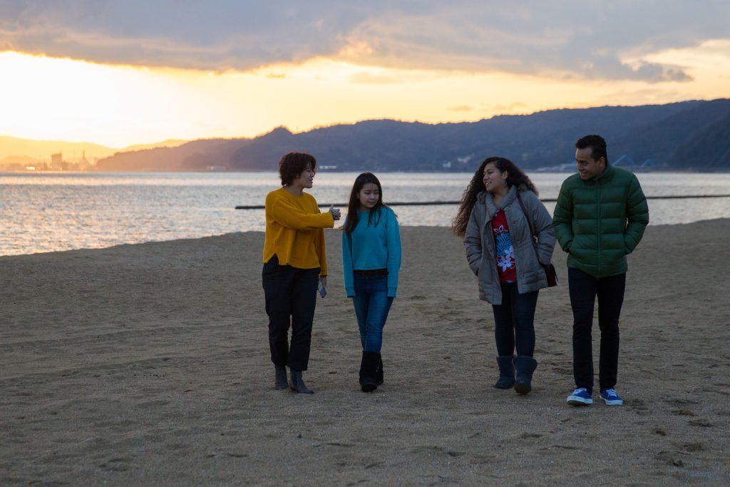 friends walking on beach in Beppu